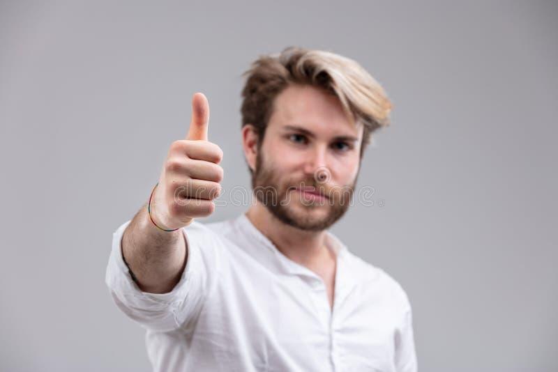 Homem com o corte de cabelo à moda que mostra o polegar acima fotos de stock royalty free