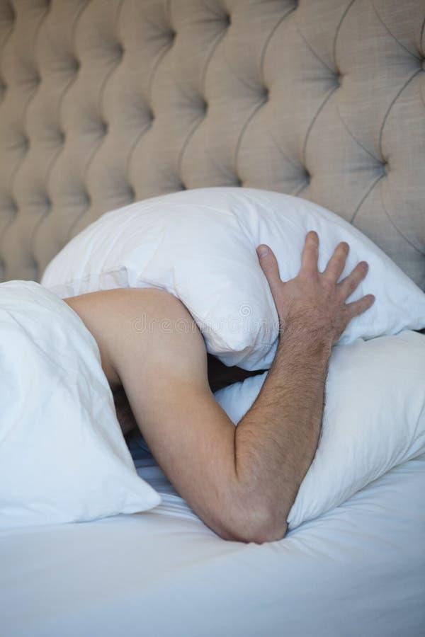 Homem com o descanso que cobre sua cara ao dormir no quarto fotografia de stock royalty free