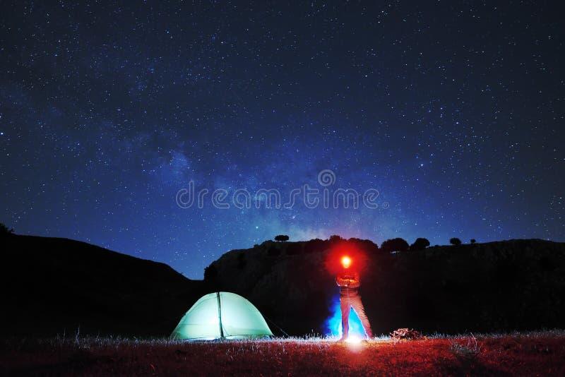 Homem com o farol vermelho que olha in camera perto da barraca da iluminação, no céu estrelado do fundo fotografia de stock royalty free