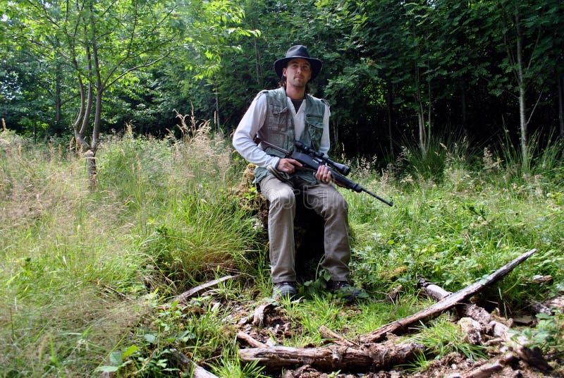 Homem com o injetor que senta-se na silvicultura imagens de stock royalty free