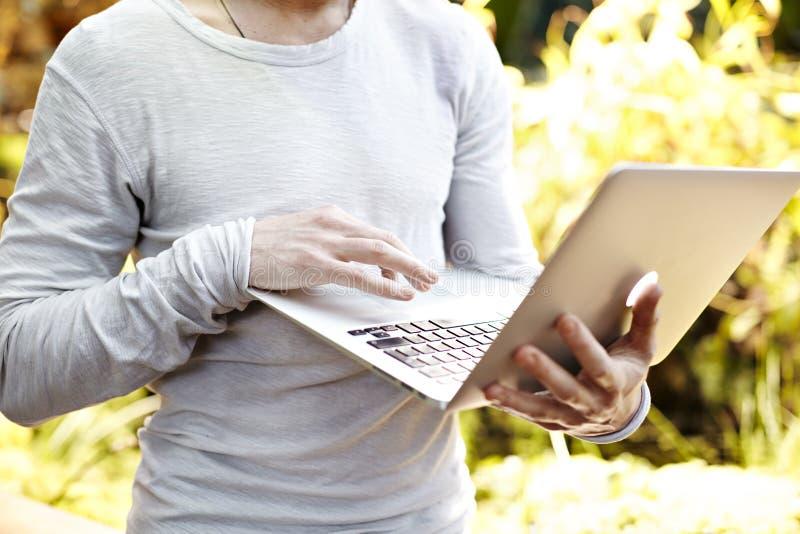 Homem com o laptop nas mãos, trabalho exterior no parque Opinião do close-up no teclado Dia ensolarado, conceito do negócio imagens de stock royalty free