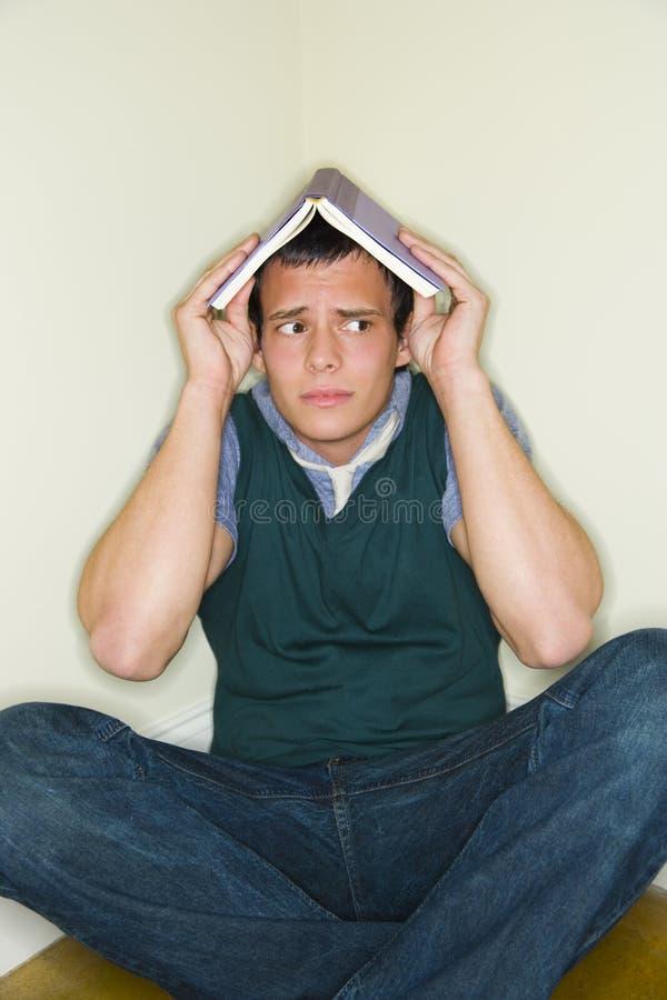 Homem com o livro em sua cabeça fotografia de stock royalty free