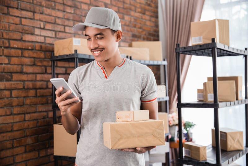 Homem com o pacote que guarda o smartphone foto de stock