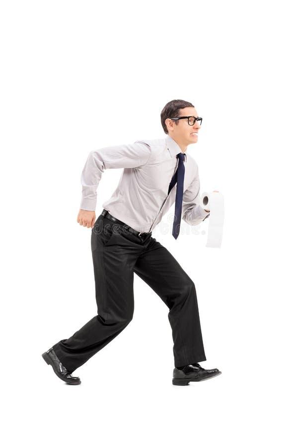 Homem com o papel higiênico que apressa-se a um banheiro fotos de stock royalty free