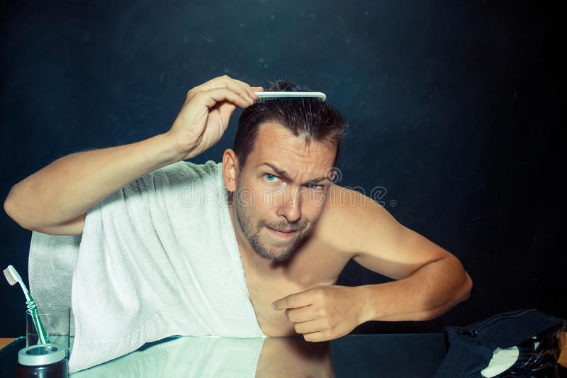 Homem com o pente referido sobre a queda de cabelo fotografia de stock royalty free