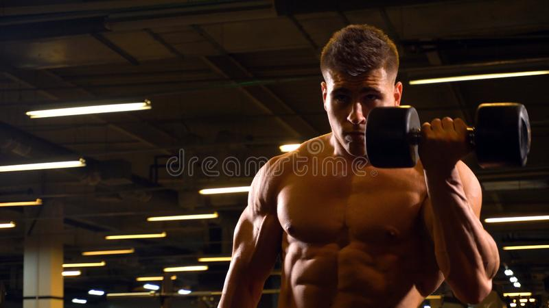 Homem com o peso que faz o exercício no bíceps fotos de stock