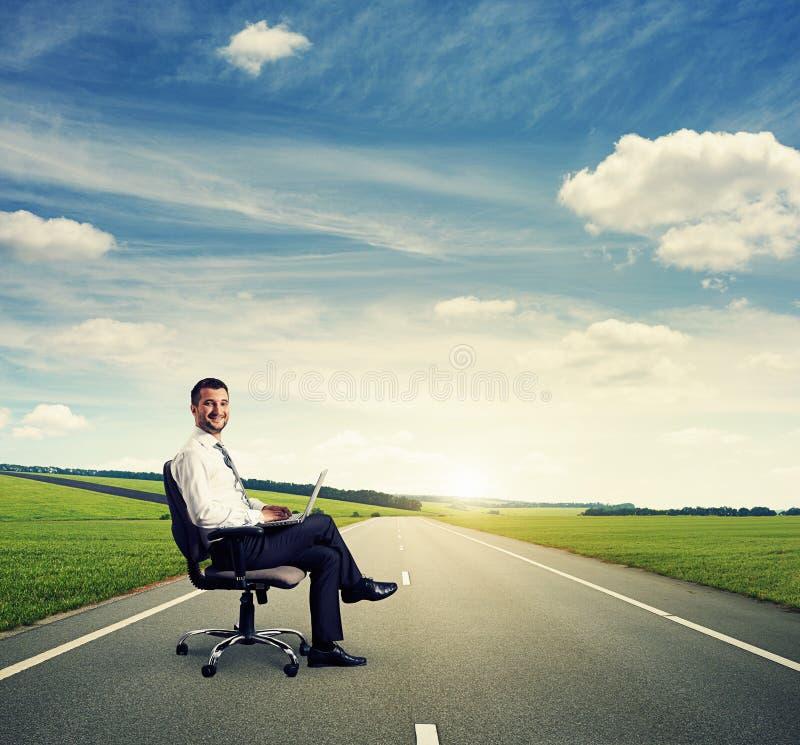 Homem com o portátil na estrada fotografia de stock
