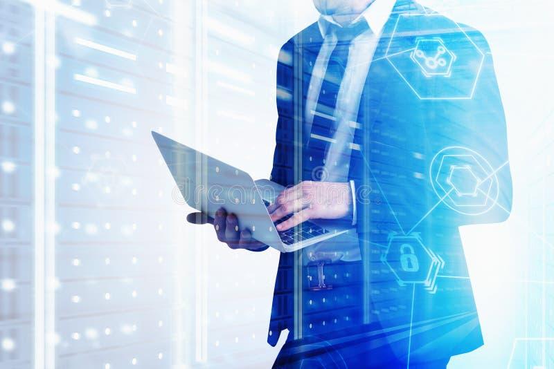 Homem com o portátil na sala do servidor, segurança do cyber fotografia de stock royalty free