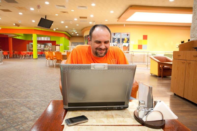Homem com o portátil no restaurante fotografia de stock royalty free