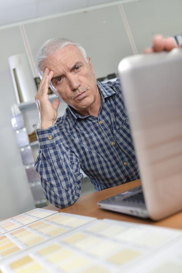 Homem com o portátil que olha incomodado imagem de stock royalty free