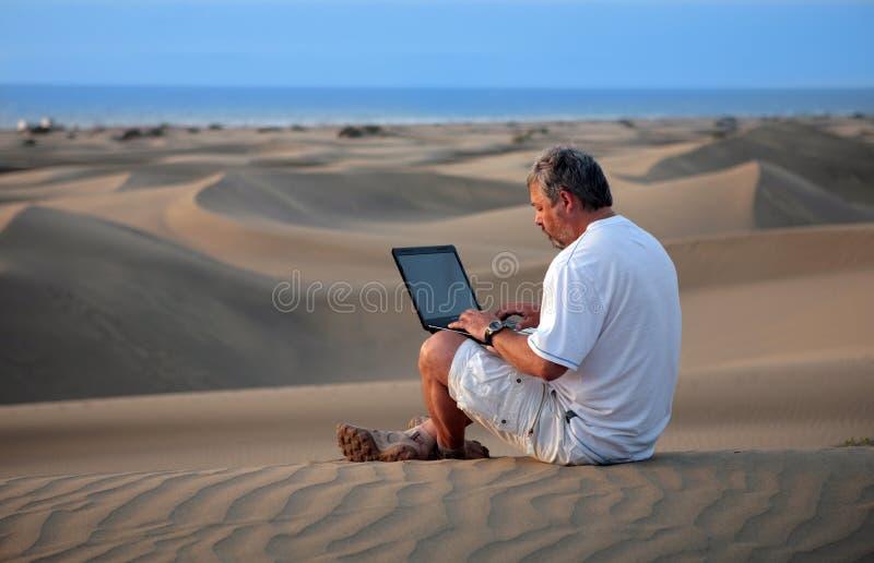 Homem com o portátil que senta-se no deserto. imagens de stock royalty free