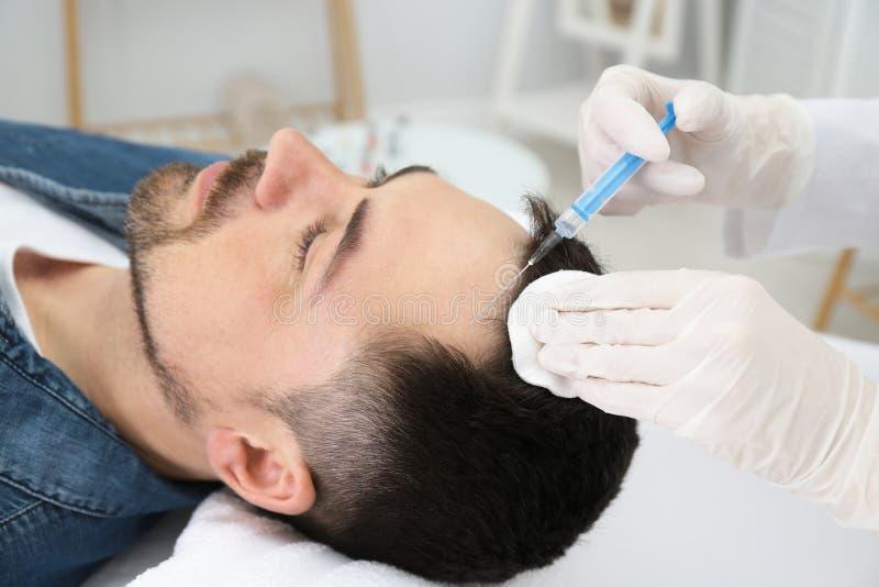 Homem com o problema da queda de cabelo que recebe a inje??o imagem de stock royalty free