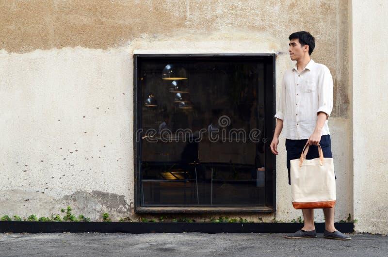 Homem com o saco da lona no fundo do concreto do grunge fotos de stock royalty free