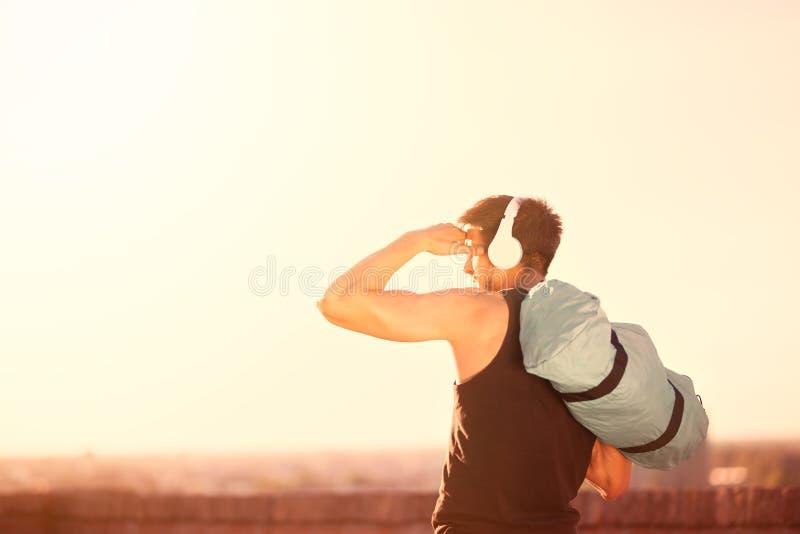 Homem com o saco do esporte que vai no treinamento sobre o dia ensolarado imagem de stock royalty free
