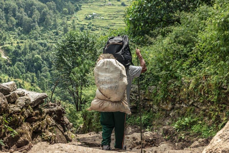Homem com o saco na rota trekking de Annapurna foto de stock