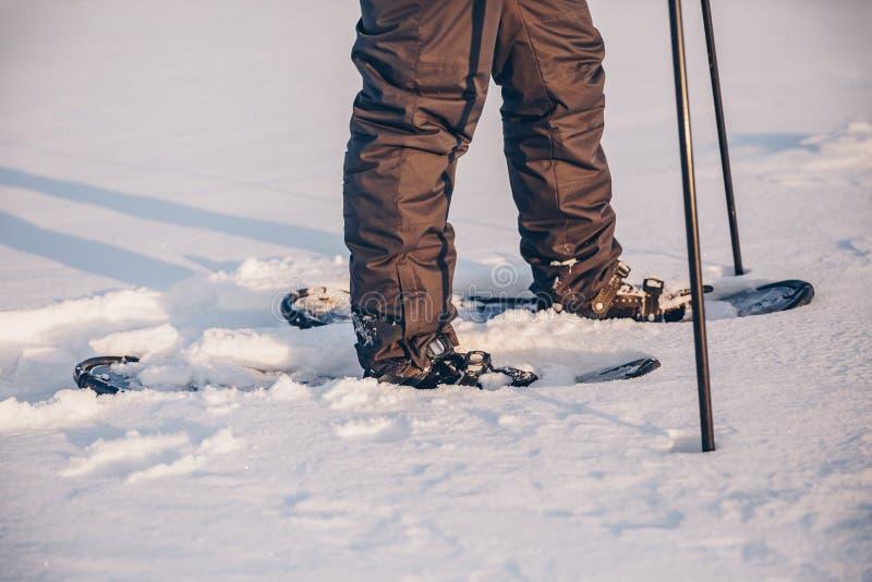 Homem com o sapato de neve no close-up do trajeto da neve Homem nos sapatos de neve com os polos trekking no inverno fotografia de stock royalty free