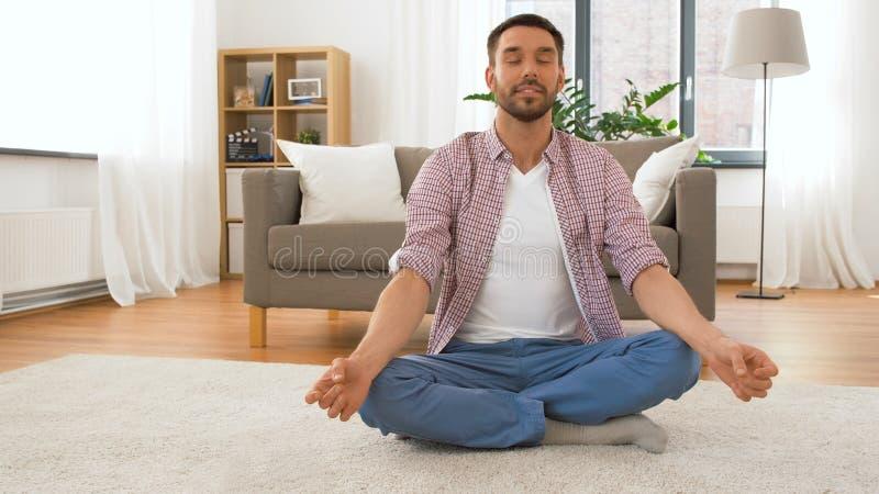 Homem com o tablet pc que medita em casa imagens de stock