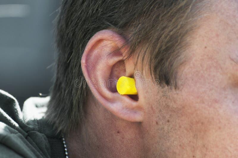 Homem com o tampão de ouvido amarelo em sua orelha fotografia de stock