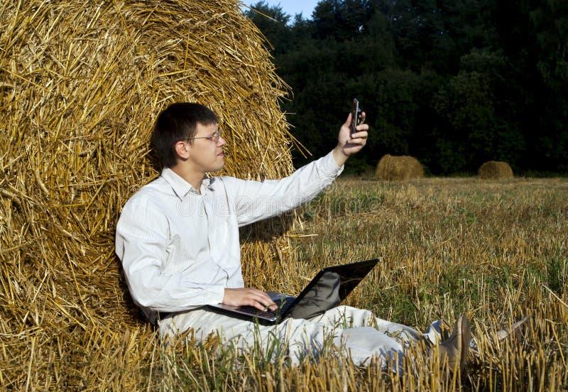 Homem com o telefone do portátil e de pilha fotografia de stock royalty free