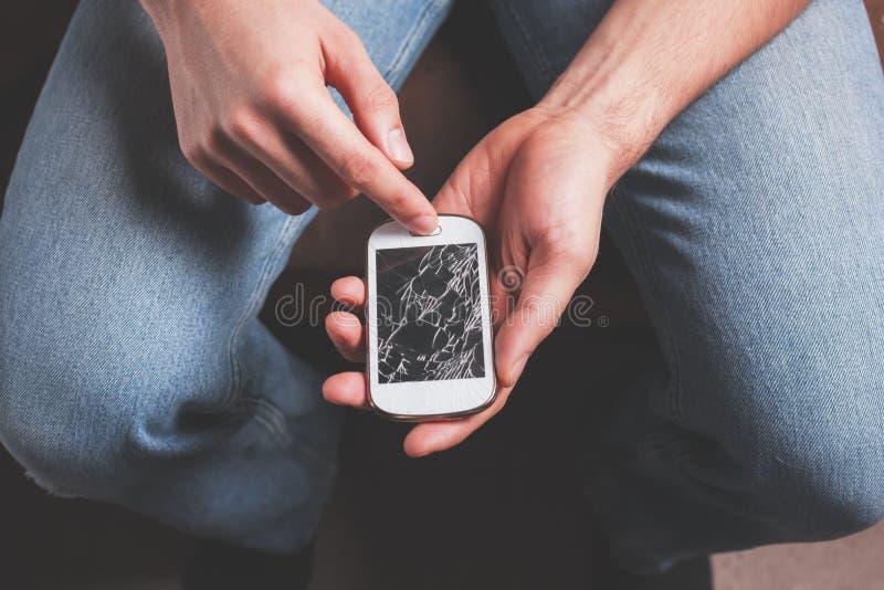 Homem com o telefone esperto quebrado imagem de stock royalty free