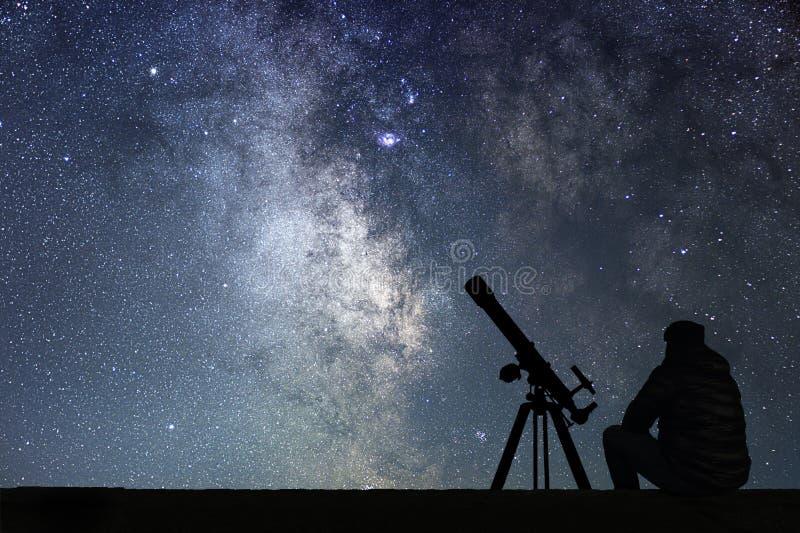 Homem com o telescópio da astronomia que olha as estrelas foto de stock