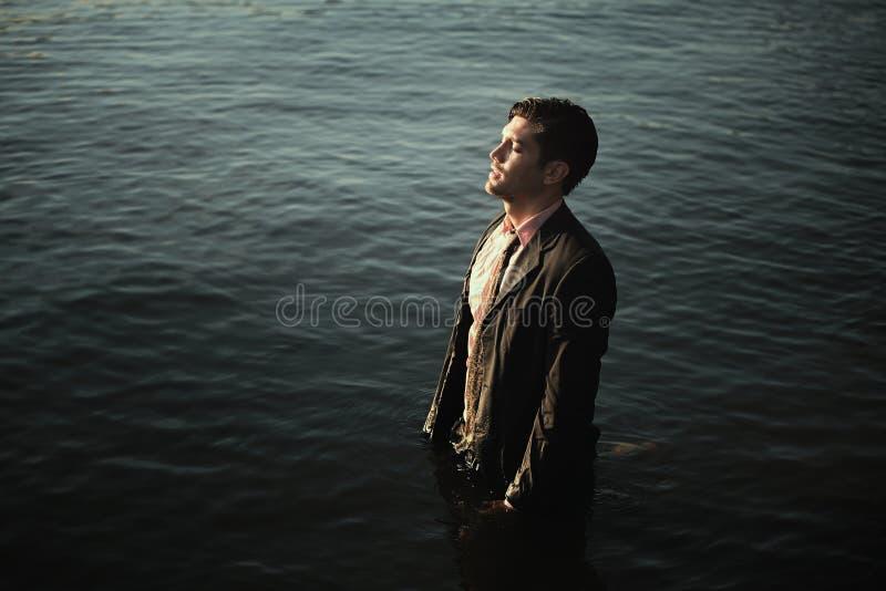 Homem com o terno de negócio nas águas do mar imagens de stock