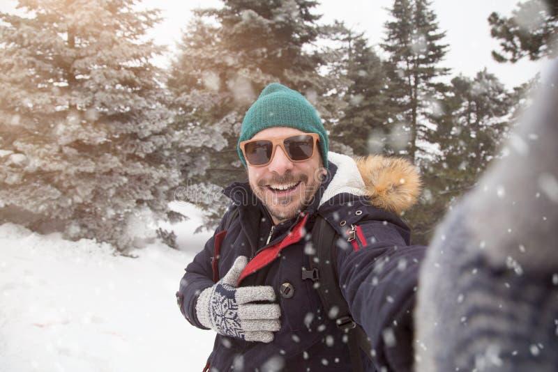 Homem com os óculos de sol que tomam o selfie no dia nevado fotografia de stock