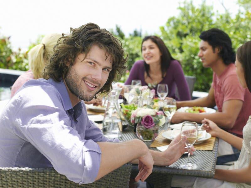 Homem com os amigos que têm a refeição fora foto de stock royalty free