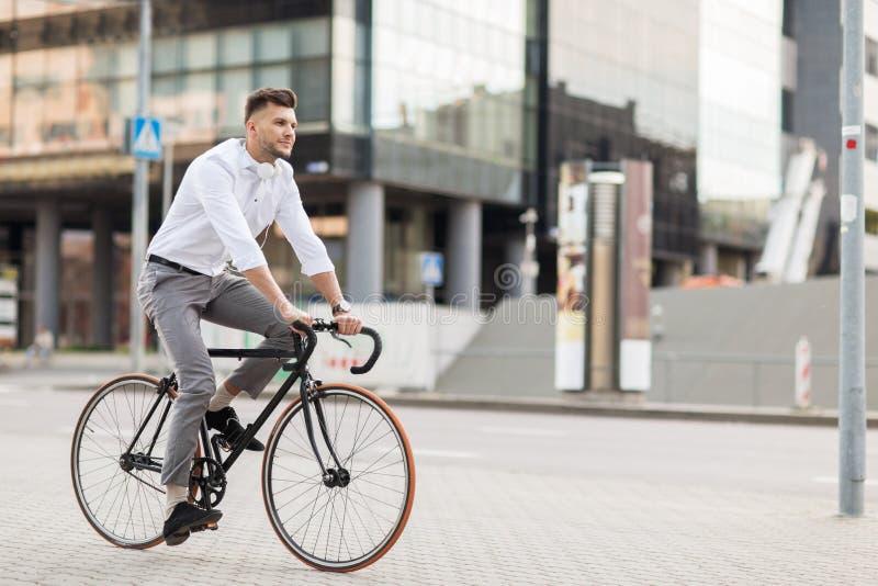 Homem com os fones de ouvido que montam a bicicleta na rua da cidade foto de stock royalty free