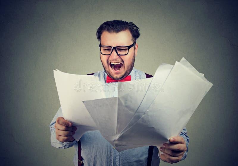 Homem com os papéis que olham irritados imagens de stock