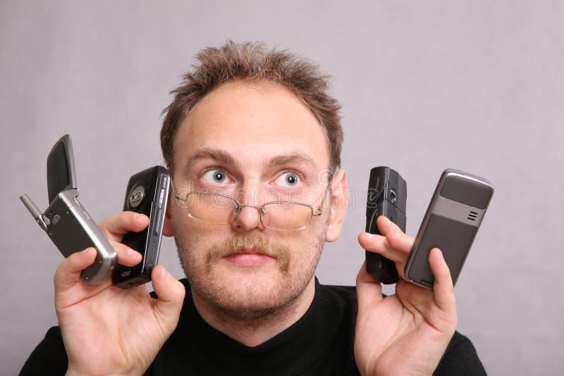 Homem com os quatro telefones de pilha fotografia de stock