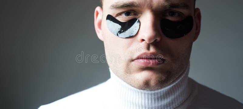Homem com os remendos do olho roxo pr?ximos acima da cara Tratamento da beleza Cuidado de pele Conceito do Metrosexual Tratamento fotos de stock