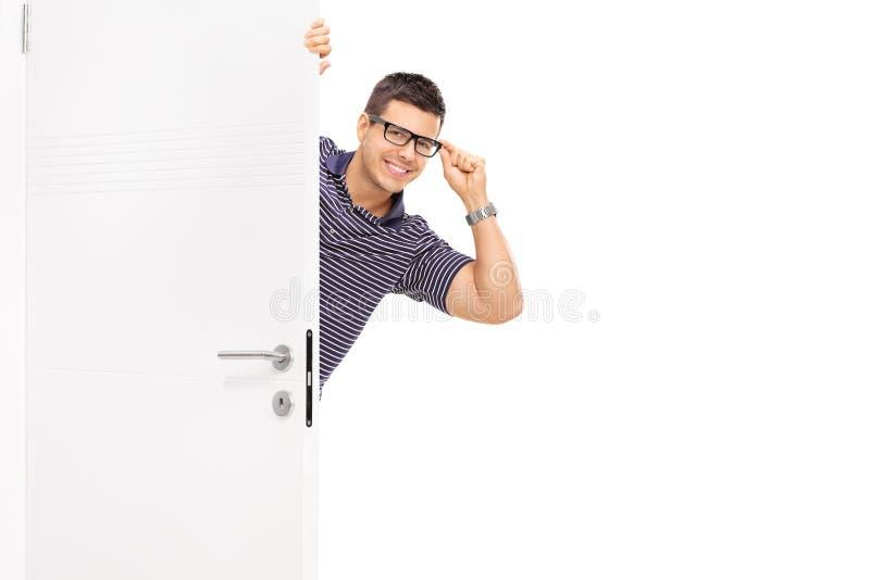 Homem com os vidros que espreitam atrás de uma porta imagens de stock