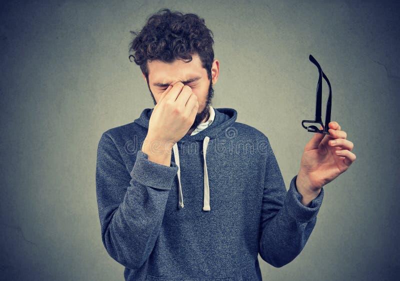 Homem com os vidros que sofrem da fadiga ocular imagem de stock