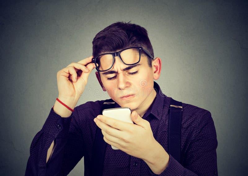 Homem com os vidros que têm o problema que vê problemas da visão do telefone celular fotos de stock royalty free