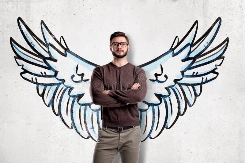 Homem com os vidros que vestem a roupa ocasional com as asas tiradas na parede no fundo ilustração do vetor