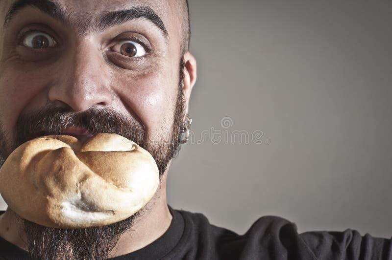Homem com pão em sua boca fotos de stock