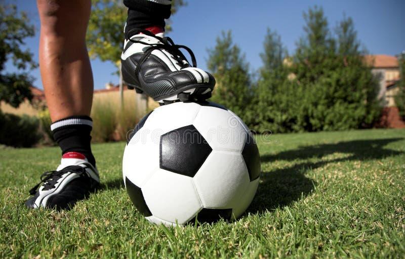 Homem com pé no soccerball fotografia de stock royalty free