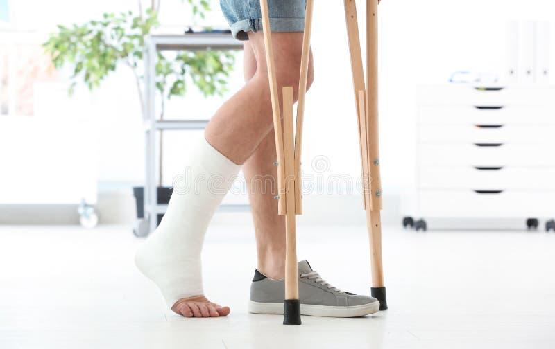 Homem com pé quebrado no molde que está em muletas fotografia de stock