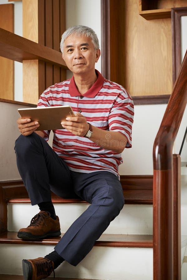 Homem com PC da tabuleta em casa fotos de stock