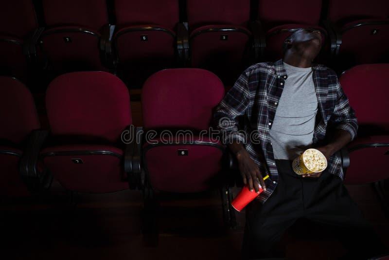 Homem com pipoca que dorme no teatro imagem de stock royalty free