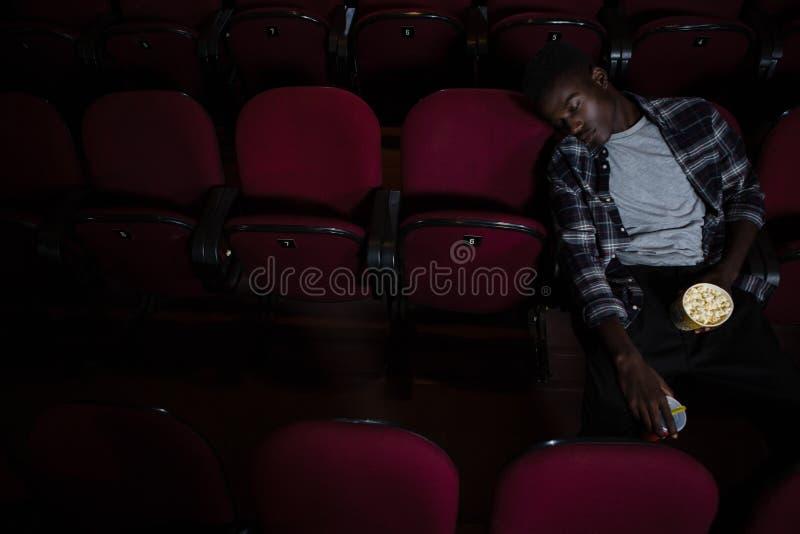 Homem com pipoca que dorme no teatro imagens de stock