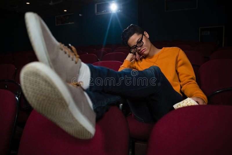Homem com pipoca que dorme no teatro fotografia de stock royalty free