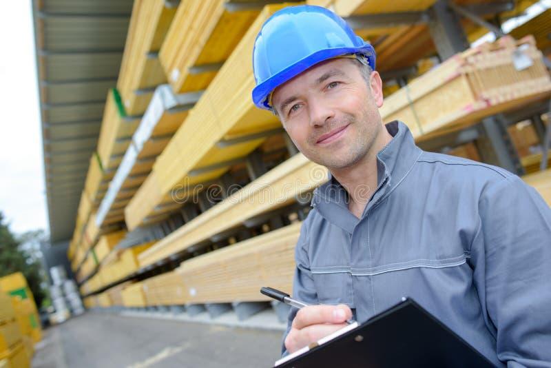 Homem com a prancheta na jarda dos construtores fotografia de stock royalty free