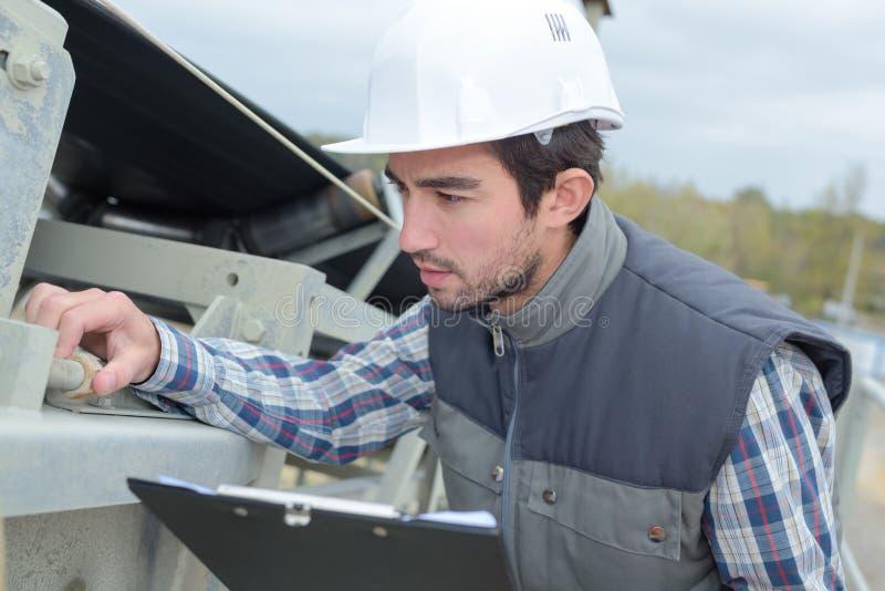 Homem com a prancheta que inspeciona o parafuso na estrutura do metal imagens de stock royalty free