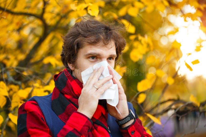 Homem com rhinitis frio no fundo do outono Estação de gripe da queda IL fotografia de stock