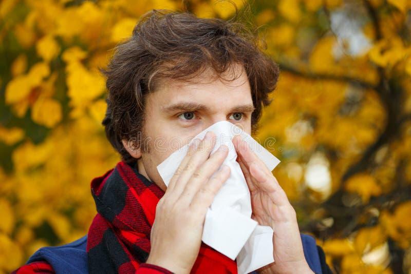 Homem com rhinitis frio no fundo do outono Estação de gripe da queda IL imagem de stock royalty free
