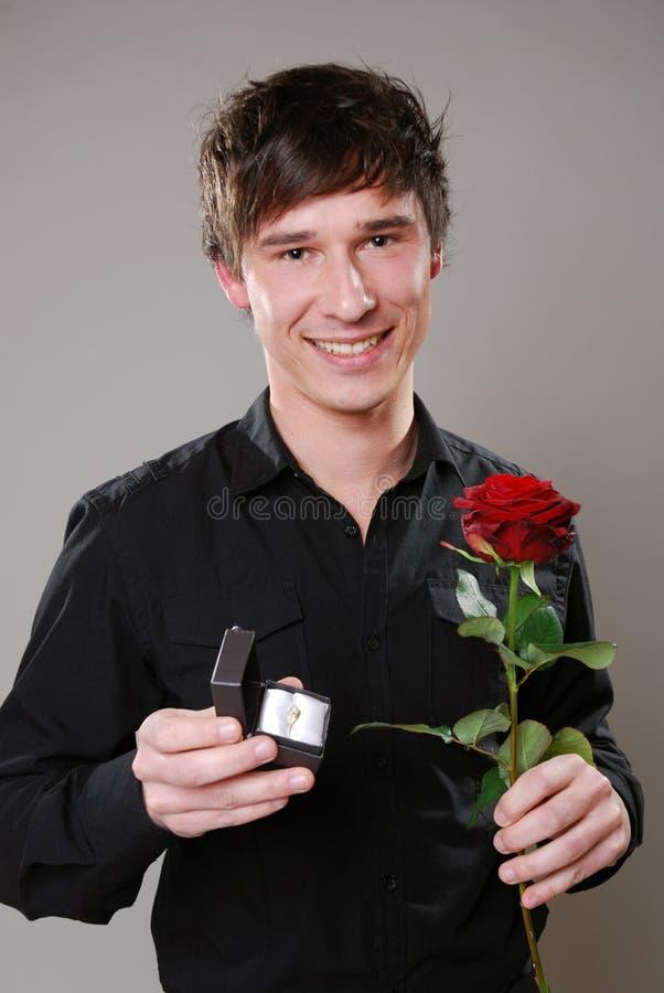 Homem com rosa e anel de casamento foto de stock
