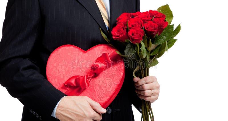 Homem com rosas e coração com chocolates no branco fotos de stock