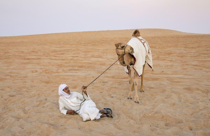 Homem com seu camelo em um deserto foto de stock royalty free